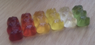 Row of gummi bears with colours in the following order: dark red, red, orange, yellow, white, green